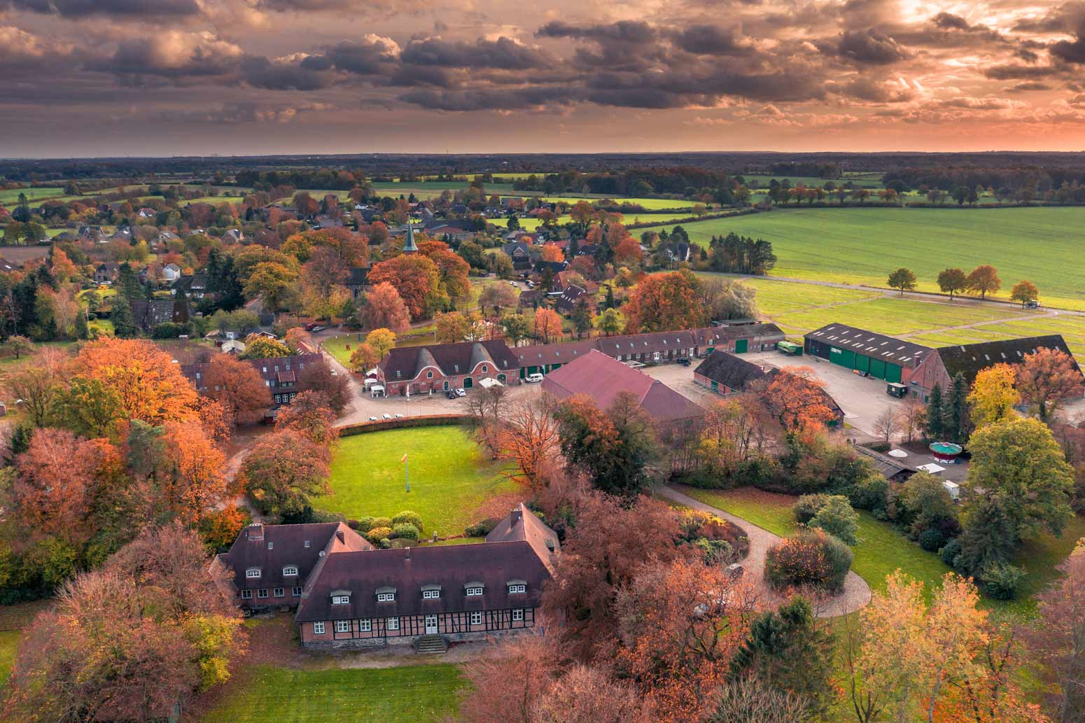 Die Jagdschule auf dem Gut Basthorst bei Hamburg im Herbst bei Sonnenuntergang aus Norden in Richtung. Rechts der Sonnenuntergang über Hamburg.