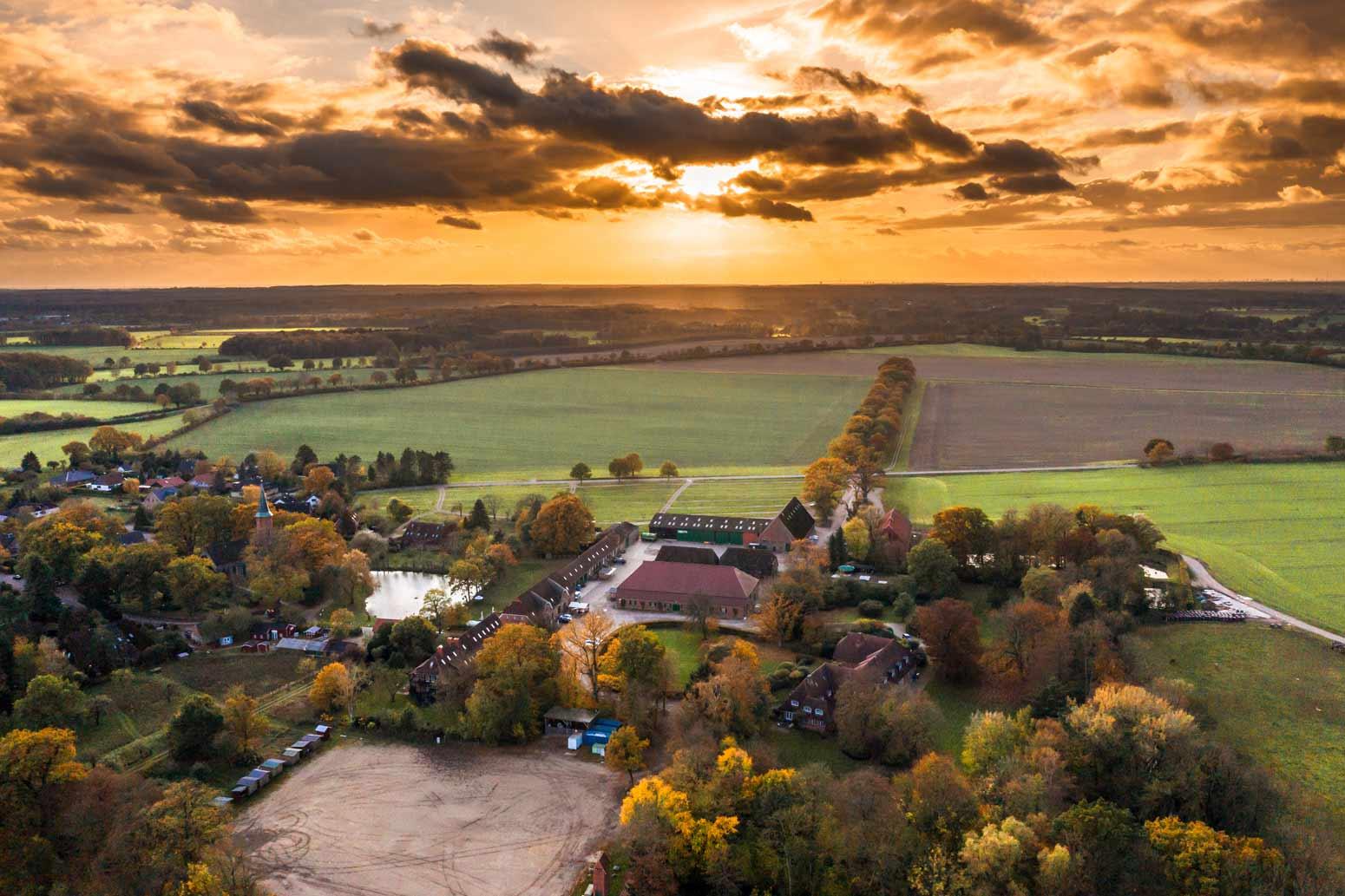 Die Jagdschule auf dem Gut Basthorst bei Hamburg im Herbst bei Sonnenuntergang aus Osten in Richtung Hamburg. Die Sonne am Abendhimmel nach einem Regenfall.