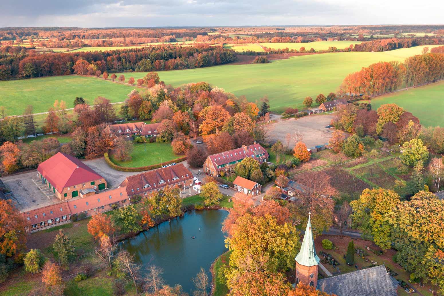 Die Jagdschule auf dem Gut Basthorst bei Hamburg im Herbst bei Sonnenuntergang aus Süden.Die Gutswirtschaft Pferdestall, die Jagdschule, die Kirche sowie das Gut Basthorst.